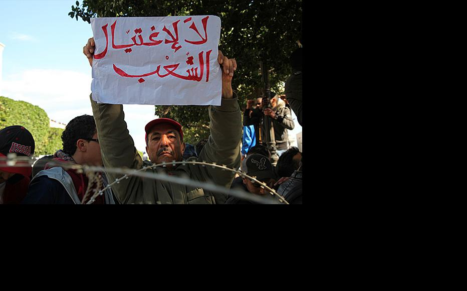 """Protestor in Tunis holds sign saying """"No to killing the people"""". (Photo: Lassad Ben Achour/Jadal.tn)"""