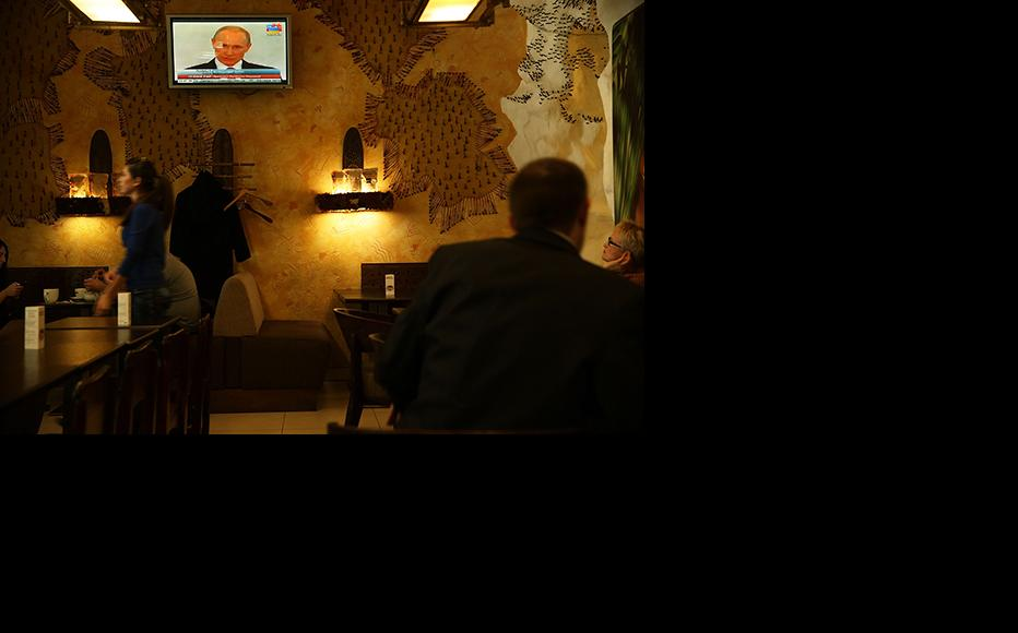 Russian President Vladimir Putin is viewed on a television screen in a cafe in Simferopol, Ukraine. (Photo: Spencer Platt/Getty Images)