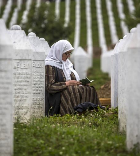 A woman prays at the Potocari cemetery and memorial near Srebrenica on July 9, 2015 in Srebrenica, Bosnia and Herzegovina.