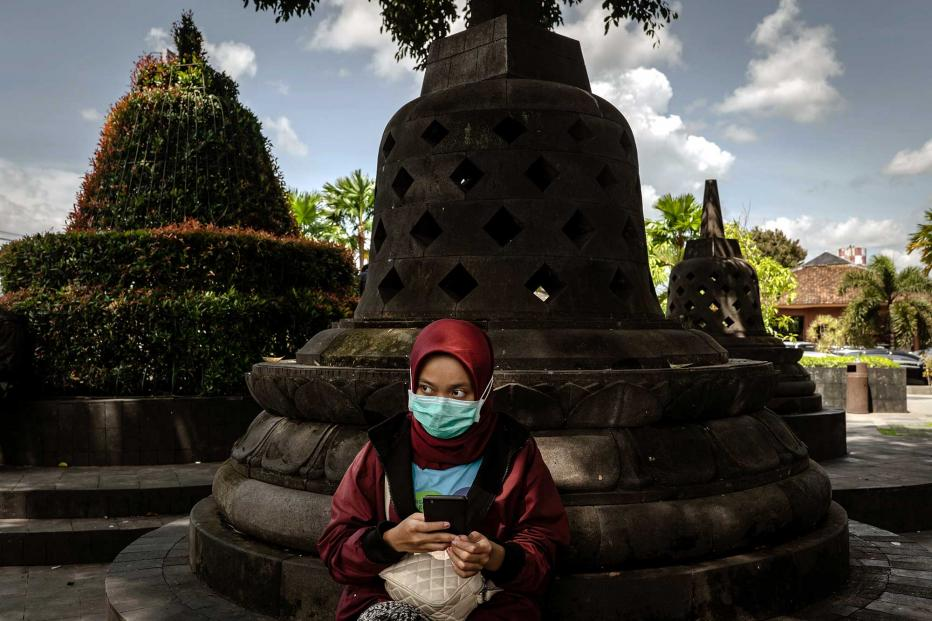 A woman wears a protective mask sits at Adisucipto International Airport on March 16, 2020 in Yogyakarta, Indonesia.