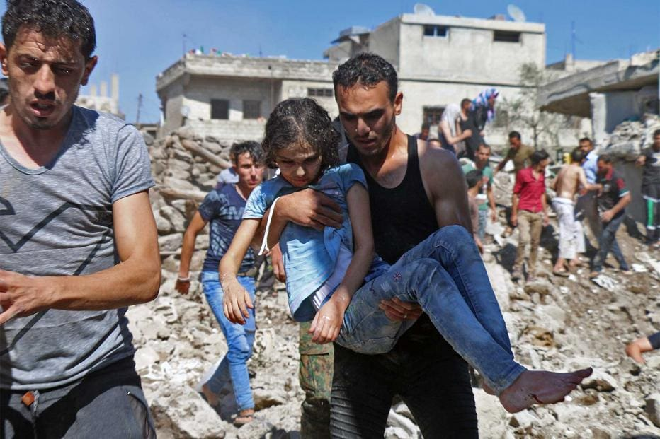 A man carries a child rescued from rubble after Syrian regime and Russian air strikes in the rebel-held town of Nawa in southern Syria on June 26, 2018.