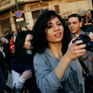 A woman takes a picture of the crowd in Tahrir Square Feburary 12, 2011 in Cairo, Egypt.