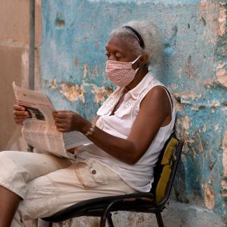 A woman wearing a face mask reads a newspaper in a street of Havana, on July 29, 2020.