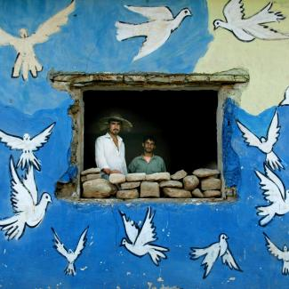 Northern Iraqi Kurds Hendrin Usman (L) and Ubeid Hasen look out a window of their house adorned with doves June 16, 2003 in a village near Erbil, Iraq.