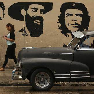 A young woman talks on her mobile phone as she walks past a mural depicting (L-R) Cuban Comunist Party founder Julio Antonio Mella and Cuban revolutionary leaders Camilo Cienfuegos and Che Guevara in the Habana Vieja neighborhood January 24, 2015 in Havana, Cuba.