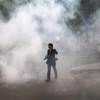 A journalist walks through smoke after violence broke out between pro-Russian activist and pro-government supporters during a rally and march on April 28, 2014 in Donetsk, Ukraine.