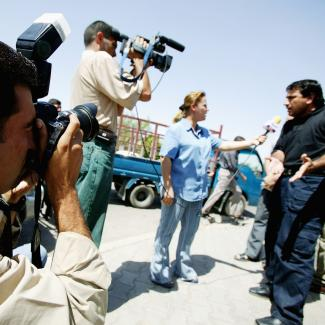 Freelance Iraqi photographer Wathiq Khuzaie working for Getty Images, photographs an interview that is taking place as part of a trial story June 30, 2004 in Baghdad, Iraq.