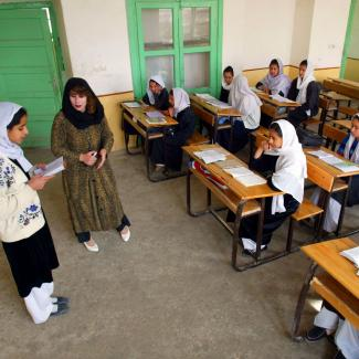 Najla listens as a student in her 4th grade class reads an excerpt from a book February 25, 2002 in Kandahar, Afghanistan.