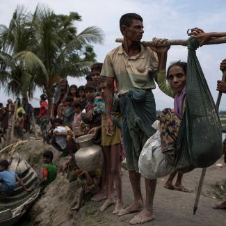 Rohingya Muslim refugees wait to board boats over a creek after crossing the Myanmar Bangladesh border on September 07, 2017 in Whaikhyang, Bangladesh.