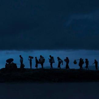 Rohingya refugees walk across Paddy fields at dusk after crossing the border from Myanmar on September 09, 2017 in Gundum, Bangladesh.