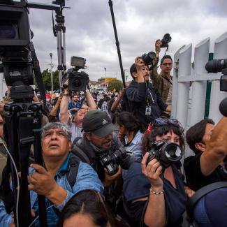 Journalists try to photograph members of a caravan of Central Americans who spent weeks traveling across Mexico as they walk towards the U.S. side of the border to ask authorities for asylum on April 29, 2018 in Tijuana, Baja California Norte, Mexico.