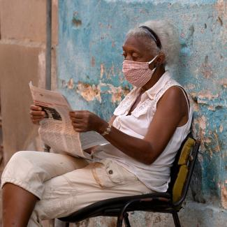 A woman wearing a face mask reads a newspaper in Havana, Cuba on July 29, 2020.