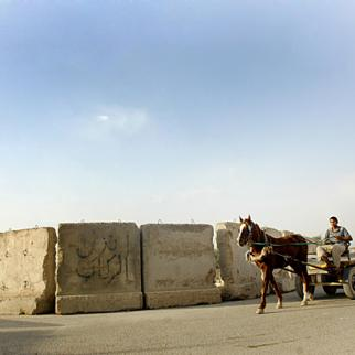 At the gates of Fallujah, a man rides past blast walls in his horse and cart - the preferred mode of transport for those who cannot afford cars or pick-up trucks. The city's economy has not recovered since 2004, when its streets were the scene of battles between United States-led forces and Sunni Arab insurgents.