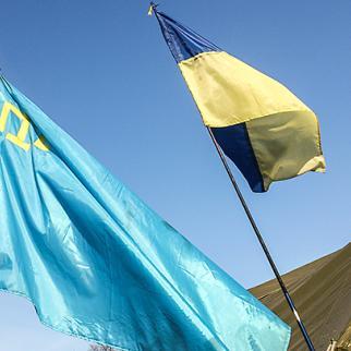 Crimean Tatar banner (left) beside the Ukrainian national flag. (Photo: John MacLeod)