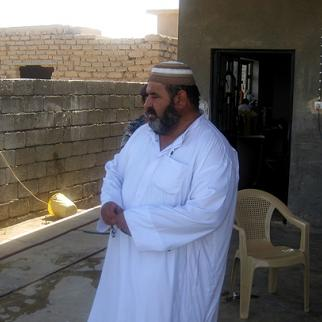 Abdul Hakeem Ahmed al-Daraji, older brother of Hameed al-Daraji, a Christian convert and former US military interpreter who was shot dead last month, watches as police search his brother's house in Samarra the day after he was killed. Security officials say the victim's son confessed to the killing. (Photo: Mahmud Salih)