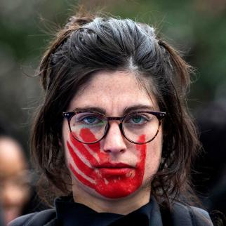 A woman wears red face paint depicting a hand during a pro women's rights protest.