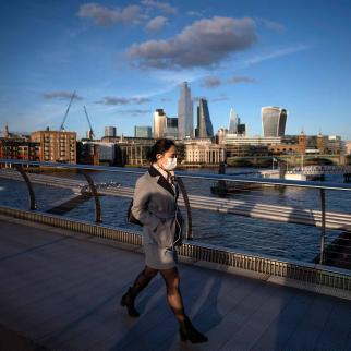 A woman crosses the Millennium Bridge in London wearing a face mask for protection against the coronavirus on March 16, 2020.