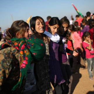 Yazidi refugees celebrate news of the liberation of Sinjar from ISIS extremists, while at a refugee camp on November 13, 2015 in Derek, Rojava, Syria. The Islamic State captured Sinjar in August 2014, killing many and sexually enslaving thousands of Yazidi women.