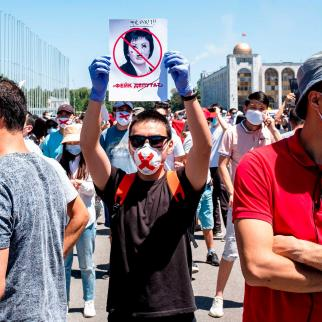 Hundreds of Kyrgyz protest against a draft law they say will hit press and internet freedoms with a man holding up a portrait of MP, the bill initiator Gulshat Asylbayeva, Bishkek, June 29, 2020.