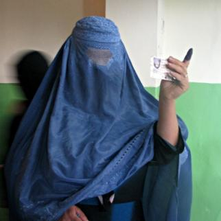 A female voter holds up a finger with ink on it showing she has voted, and preventing her from doing so again. (Photo: IWPR Afghanistan)
