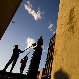 Afghan construction workers shovel cement to build a wall. (Photo: Paula Bronstein /Getty Images)