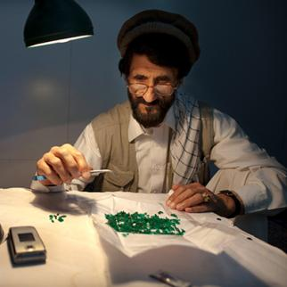 An expert examines emeralds from an Afghan mine. The mineral resources of Afghanistan are relatively unexplored even with Afghanistan's wealth of coal, copper, gold and iron ore, with precious and semiprecious stones. (Photo: Paula Bronstein/Getty Images)
