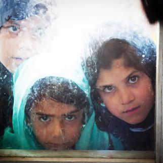 Afghan girls look through a window of a classroom in Kabul,. (Photo: Majid Saeedi/Getty Images)