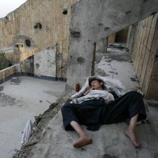 A homeless heroin addict sleeps outside on the ledge of an abandoned building in Kabul. (Photo: Paula Bronstein/Getty Images)