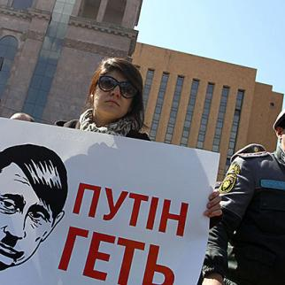 """A protest holds a banner saying """"Putin Get Out"""" during a demonstration outside the Russian embassy in Yerevan, March 5. (Photo: Photolure agency)"""