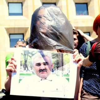 A protester in front of government buildings in Tbilisi, imitating the abduction of Afgan Mukhtarli, reportedly pushed into a car by unknown persons and a bag placed over his head. (Photo: Lib Center)