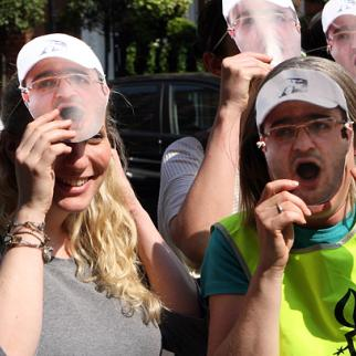 Rebecca Vincent lifts a mask of Eynulla Fatullayev from her face, while other protesters look on. (Photo: Oliver Bullough)