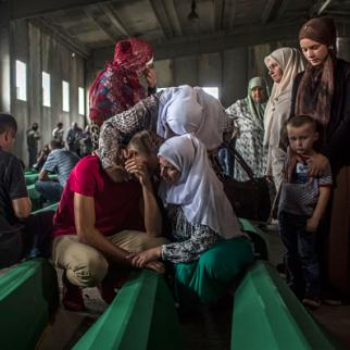A family mourn over a coffin among 136 victims of the 1995 Srebrenica massacre in the hall at the Potocari cemetery and memorial near Srebrenica on July 9, 2015. (Photo: Matej Divizna/Getty Images)