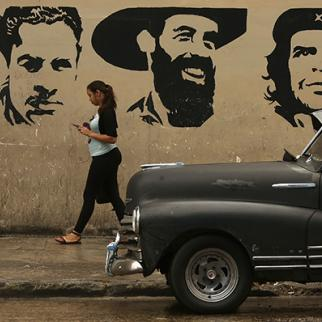 A young woman talks on her mobile phone as she walks past a mural depicting (l to r) Julio Antonio Mella, Camilo Cienfuegos and Che Guevara in Havana, Cuba. (Photo: Chip Somodevilla/Getty Images)