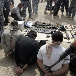Al-Qaeda suspects and their alleged weapons at Diyala police station in Baquba following an anti-insurgent operation in 2008. (Photo: Diyala Police)