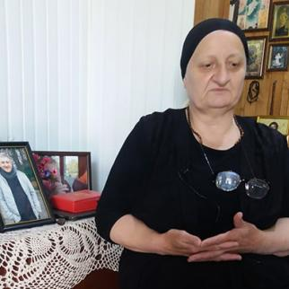 Giga Otkhozoria's mother, Julieta Chanturia, sits in her home with photos of her son. (Photo: Tamuna Shonia)