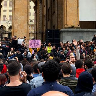 """Young people protesting in front of the parliament building in Tbilisi, condemning the raids organised by the Georgian police at Bassiani night club. Some demonstrators compared it with the Russian style crackdowns and held placards saying """"We do not need another Putin here"""". (Photo: IWPR)"""