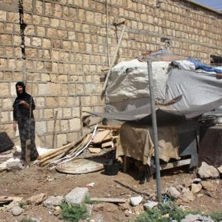 Ameena Abdullah stands outside her makeshift home where she has lived for six years in the Makbali refuge camp (Photo: Rasheed Duhok)