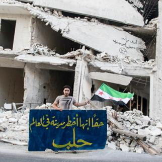 """A medical volunteer in Bustan al-Qasr district stands in front of a ruined building holding a banner that says, """"Truly, Aleppo is the most dangerous city in the world."""" (Photo: Ammar Abdullah)"""