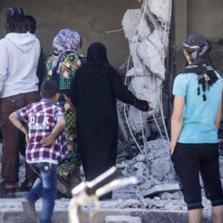 Women inspect a home in ruins targeted by the regime. (Photo: IWPR)