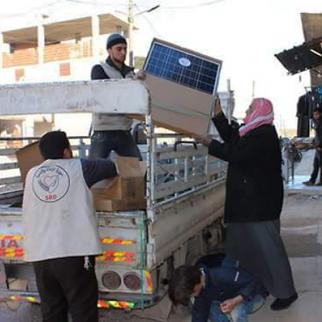 Employees of the Syria Relief and Development NGO distribute solar-powered appliances. (Photo: Shelter)