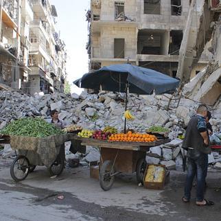 A woman buys vegetables from a street vendor in Aleppo's Al-Shaar neighbourhood. (Photo: Baraa al-Halabi)