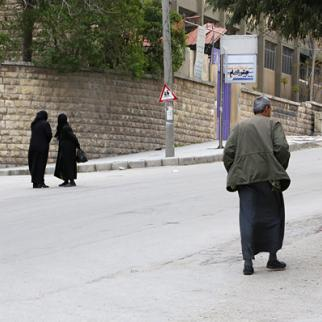 Two women stand and chat outside a school in the Ansari neighbourhood of Aleppo. (Photo: Hussam Kwaifatiya)