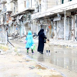 A woman and her children crossing the street in front of the remains of the al-Shaar bridge. (Photo: Hussam Kuwaifatiyeh)