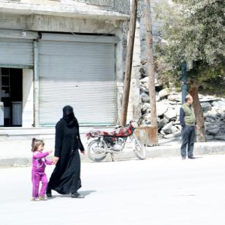 A woman and her daughter cross the street in front of a destroyed building in the al- Marja neighbourhood. (Photo: Hussam Kuwaifatiyeh)