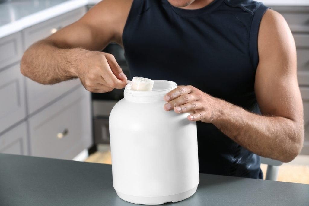Man holding plastic scoop with keto protein powder