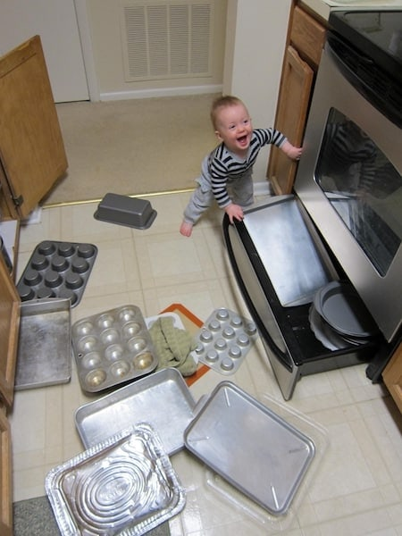 toddler smiling and making a mess for mom in the kitchen with pots and pans all over the floor