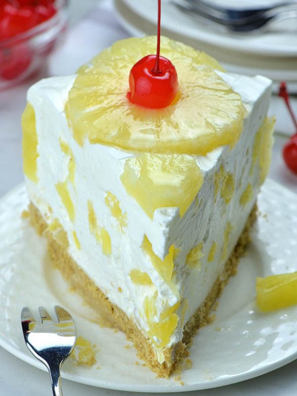 Slice of pineapple cake on white plate top with pineapple ring and maraschino cherry.
