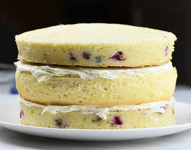 Two cranberry cake layers with cheesecake layer between.