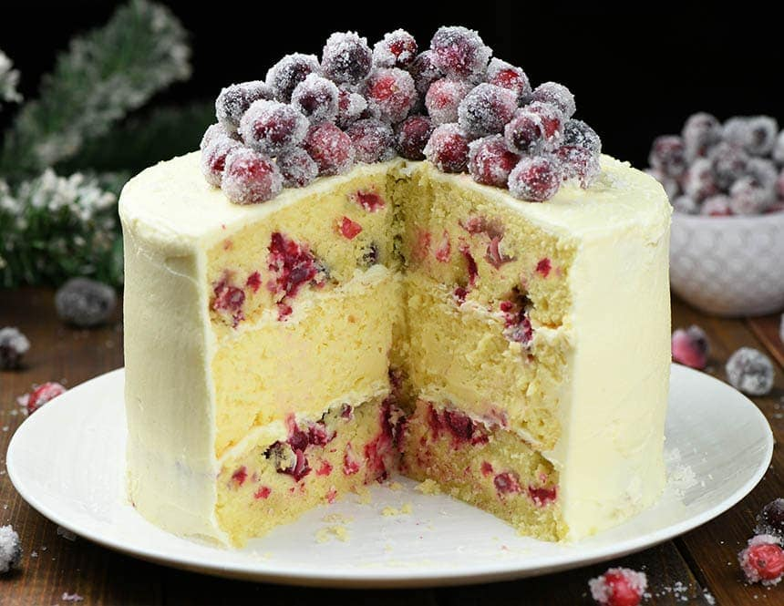 Whole White Chocolate Cranberry Cheesecake Cake with few pieces missing in the center.