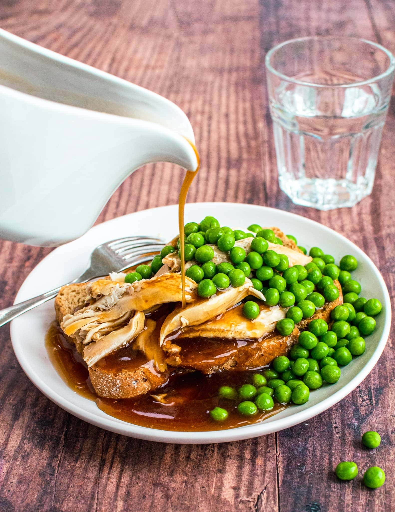 Gravy pouring on hot turkey sandwich with peas